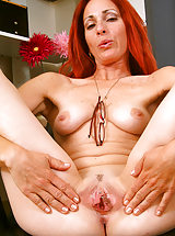 Skinny redheaded MILF Skyla strips and spreads at the office
